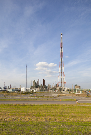 A large refinery complex with flare stack and blue sky.