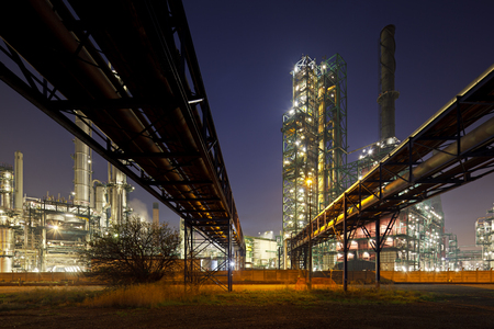 An oil refinery in the harbor of Antwerp with night blue sky, two pipelines leading towards it.
