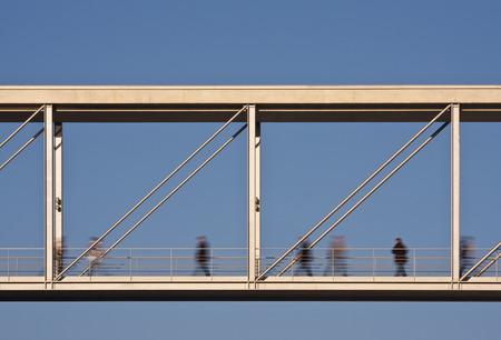 わずかに動きがぼやけた2つのオフィスビルの間の近代的な歩道橋。 写真素材