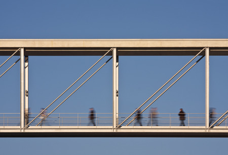 A modern pedestrian bridge between two office buildings with slightly motion blurred people.