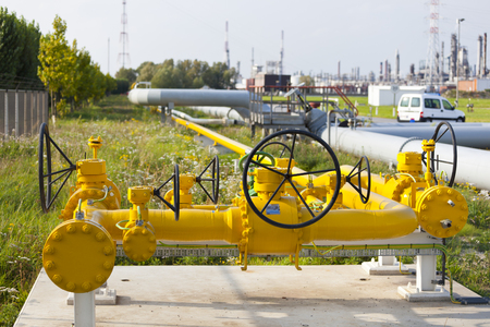 Yellow gas pipeline with valves in a refinery.