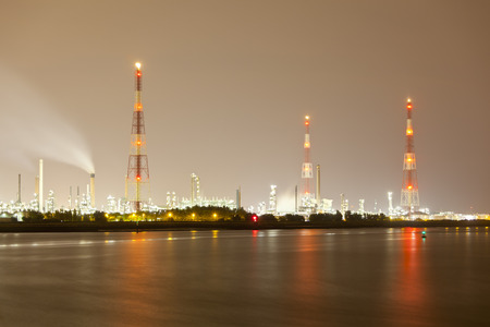 An oil refinery with tall gas flare stacks in a harbor with dirty night sky.