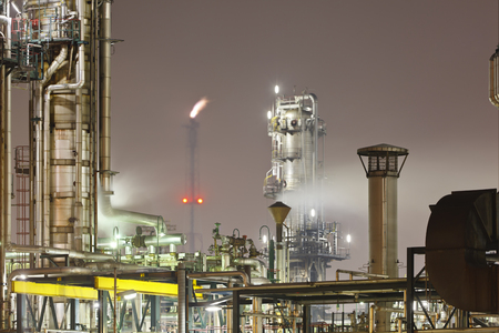 An oil refinery detail shot with a flare in the background. Stok Fotoğraf