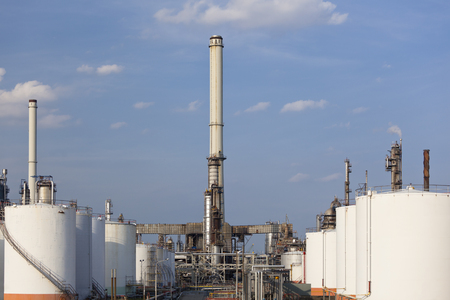 Some storage tanks and smoke stacks in a large refinery.
