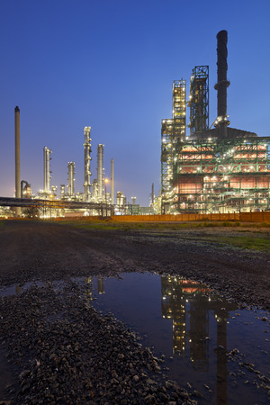 An oil refinery in the harbor of Antwerp at night with reflection in a puddle.
