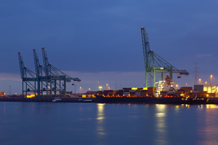 A container terminal with tall cranes. Night shot taken in Antwerp, Belgium.