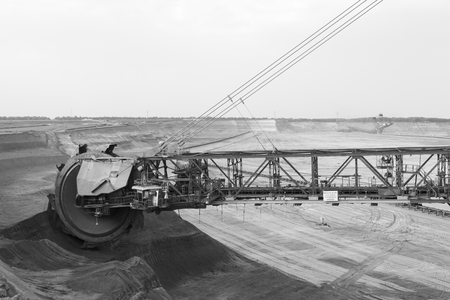 A lignite surface mine with a giant bucket-wheel excavator, one of the worlds largest moving land vehicles in black and white. The wheel has a diameter of more than 12 meters.
