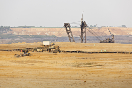 A lignite surface mine with a giant bucket-wheel excavator looking over a rim. Imagens