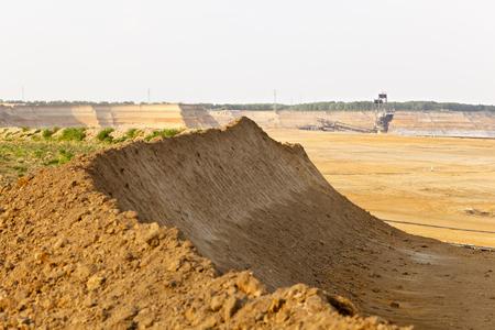 Confine di una miniera di superficie di lignite con un gigantesco escavatore a ruota a tazze, uno dei più grandi veicoli terrestri in movimento al mondo in background. Archivio Fotografico - 93401461