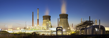 Panorama of an oil refinery with two cooling towers and blue night sky, some pipelines in the foreground.