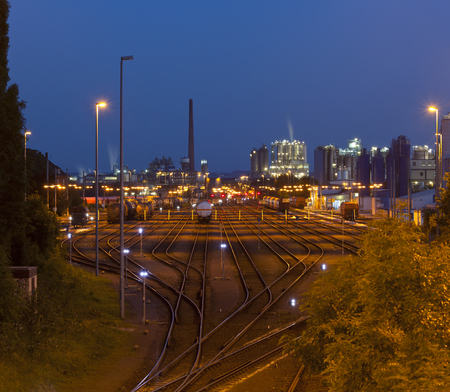 Night shot of an industrial railroad yard with several trains, a refinery in the background. Standard-Bild - 96116382
