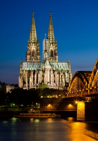 Vertical night shot of the Cologne Cathedral across the rhine river.