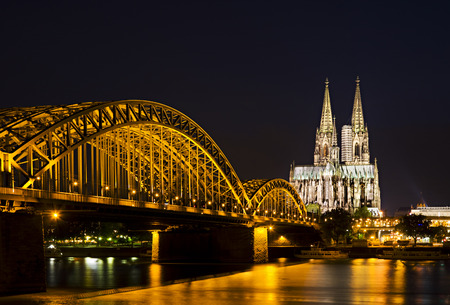 The famous Cologne Cathedral and the Hohenzollern Bridge at night.