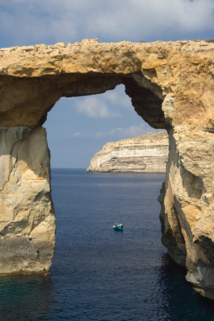 A little boat approaches the famous Azure Window on Gozo, Malta. Banco de Imagens