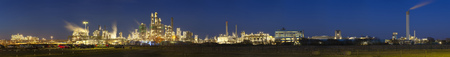 Panorama of an oil refinery with blue night sky, a parking lot in the foreground.