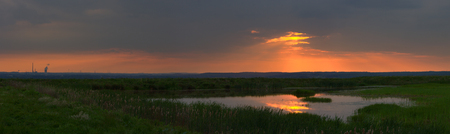 Sunset Panorama with a small lake on an artificial hill, Germany.