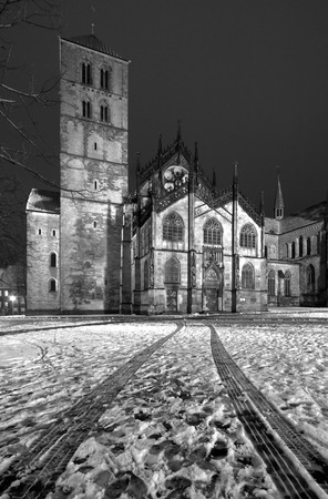 Wide angle perspective of the famous cathedral in Muenster, Germany. The wheel tracks in the snow are leading to the gate. Editorial