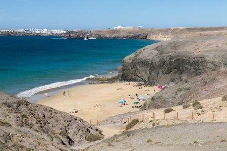 LANZAROTE - JANUARY 13: The beautiful beach Playa de la Cera in Lanzarote, Spain with some hotels in the background on January 13, 2016.