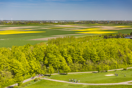 INDEN - MAY 5: Aerial view of people playing soccer golf and going for a walk in green landscape with some yellow rape fields in the background on May 5, 2016.