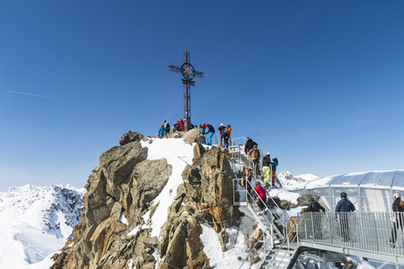 SOELDEN - MARCH 22: The summit cross on the Gaislachkogel in the Oetztal, Austria with lots of tourists on March 22, 2016.