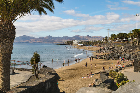 LANZAROTE - JANUARY 4: Playa Grande in Puerto del Carmen in Lanzarote, Spain with tourists enjoying the sun on January 4, 2016.