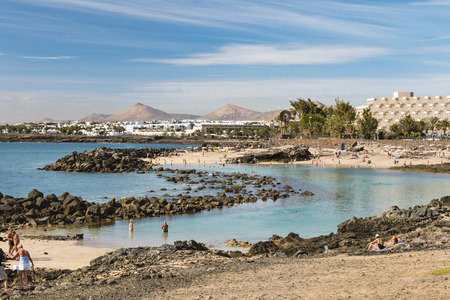 LANZAROTE - JANUARY 14: People at a lagoon at Costa Teguise Beach in Lanzarote, Spain with the village in the background on January 14, 2016. Editorial