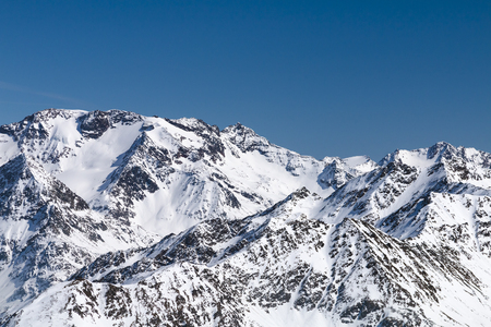 View from the Gaislachkogel in the Oetztal, Austria with snow covered mountain landscape and blue sky.