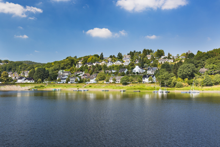 Rurberg lake front at Lake Rursee with perfect blue sky and marinas in summer.