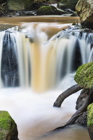Long exposure detail shot of a small Nairobi River waterfall in Karura Forest, Kenya.