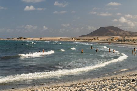 FUERTEVENTURA - SEPTEMBER 19: Tourists enjoying the waves at Corralejo Beach in Fuerteventura, Spain on September 19, 2015 Editorial