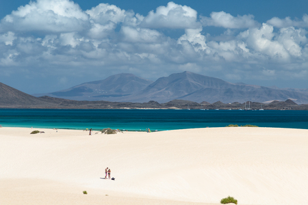 FUERTEVENTURA - SEPTEMBER 29: A young couple in the Corralejo sand dunes by the sea in Fuerteventura, Spain with Lanzarote in the background on September 29, 2015 Editorial