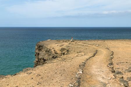 FUERTEVENTURA - SEPTEMBER 26: A female tourist on a tall cliff near El Cotillo in Fuerteventura, Spain on September 26, 2015 Editorial