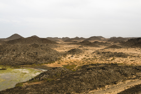 A small brackish water lake on the Isla de Lobos in Fuerteventura, Spain with the typical moon like volcanic landscape of the island. 스톡 콘텐츠 - 100026507