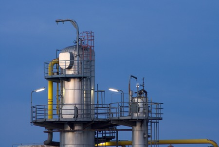 Towers of an oil refinery and chemical plant in the evening.