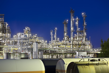 A large oil refinery with railroad cars as foreground at night.