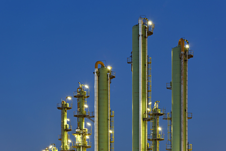 Green distillation towers on blue sky at night.