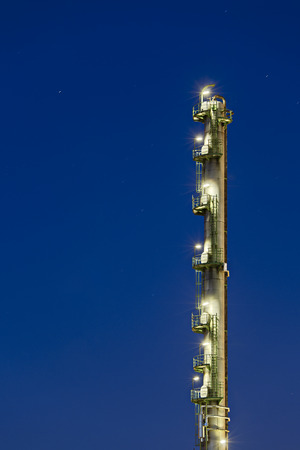 A tall distillation tower isolated on blue night sky with a lot of copyspace. Stok Fotoğraf
