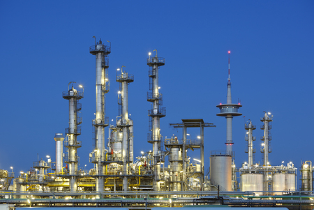 A chemical plant at with night blue sky, a telecommunications tower in the background. Stok Fotoğraf