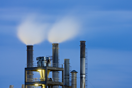 Smoke stacks of a chemical plant with night blue sky. Editöryel
