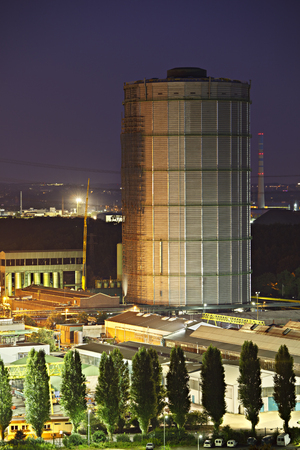 A more than 100m tall gasometer building of an industrial site at night.
