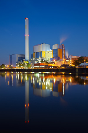 An incineration plant at a canal at blue hour in the night. Strong colors and clear reflection.