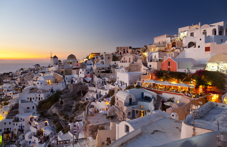 The famous windmills of Oia in the west of Santorini with a colorful sunset. Editorial