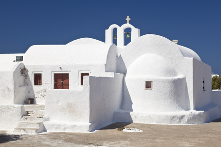 A little chapel next to the Sotiras Church of Oia with deep blue sky. Santorini, Greece.