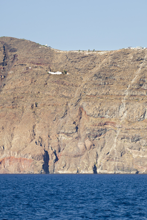 View from a boat to the tall cliffs of Santorini, Greece with a chapel in the wall. Stock Photo