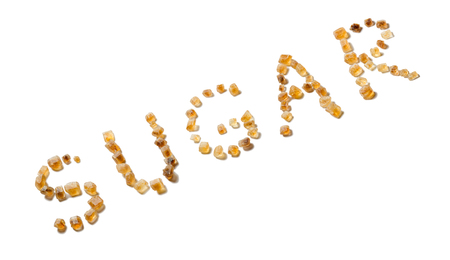 The word SUGAR spelled with brown sugar crystals isolated on white.