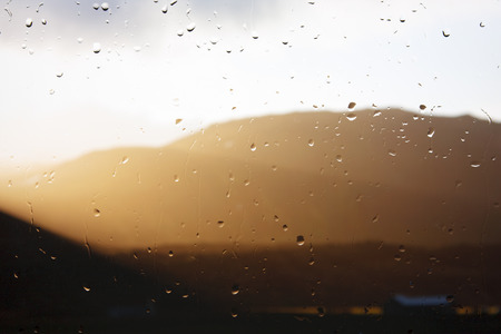 Sunlight breaking through the clouds seen through a raindrop covered window.