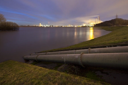 Double pipeline in Duisburg, Germany in front of Rhine River and several power stations and coking plants.