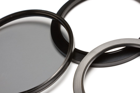 A polarizer lens filter and two step down adapter rings on white.