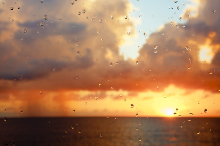 Sunset with tall clouds seen through a raindrop covered window. Stock Photo