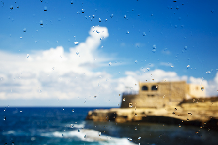A mediterranean building at the coast seen through a raindrop covered window.